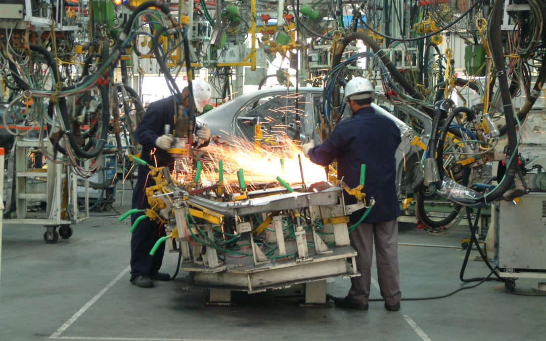 workers producing car in manufacturing plant