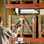 man scanning pallet with device in warehouse