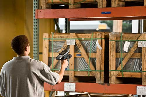 man scanning pallet with device in warehouse real time