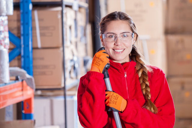 warehouse woman worker with safety glasses and gloves